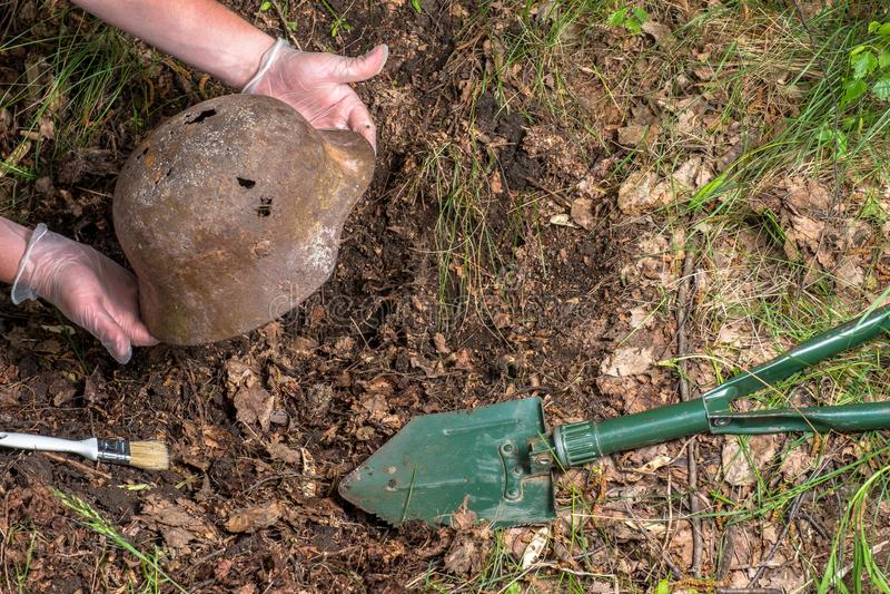 Gravend in het bos de Duitse helm M35 imitatie WW2 terugwinning Rusland royalty-vrije stock afbeeldingen