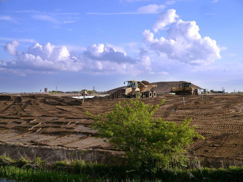 Graver en kipwagenvrachtwagen die aan de terugwinning van de afvalgrond werken stock foto