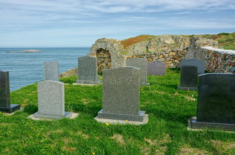 Graves on cliff edge. Final resting place with dramatic sea view. Graves and headstones on a cliff edge overlooking the sea, a final resting place with a stock image