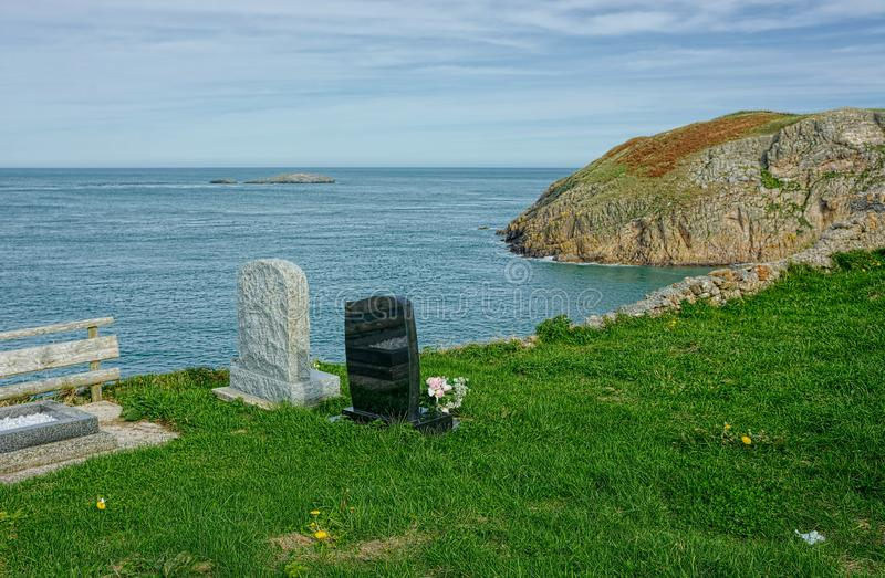 Graves on cliff edge. Final resting place with a sea view. Graves and headstones on a cliff edge overlooking the sea, a final resting place with a dramatic sea stock photography