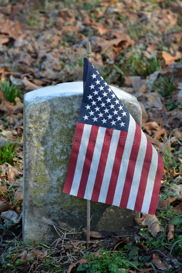 Graves of veterans. In an old cemetery marked by the American flag. From the dates on these markers, they were probably veterans of the civil war in the mid stock image