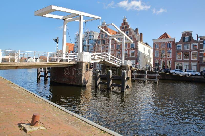 Gravestenenbrug-Brücke über Spaarne-Fluss und mit traditionellen Häusern im Hintergrund, Haarlem lizenzfreies stockbild