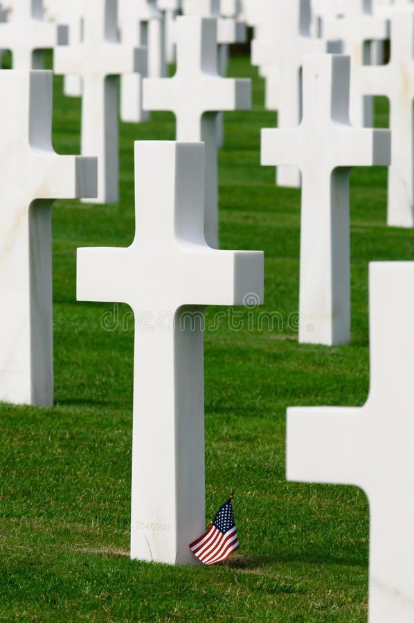 Gravestone and Flag. Closeup of crosses in the American Cemetery in Normandy, France. A small American flag is at the base of one of the grave markers stock photo