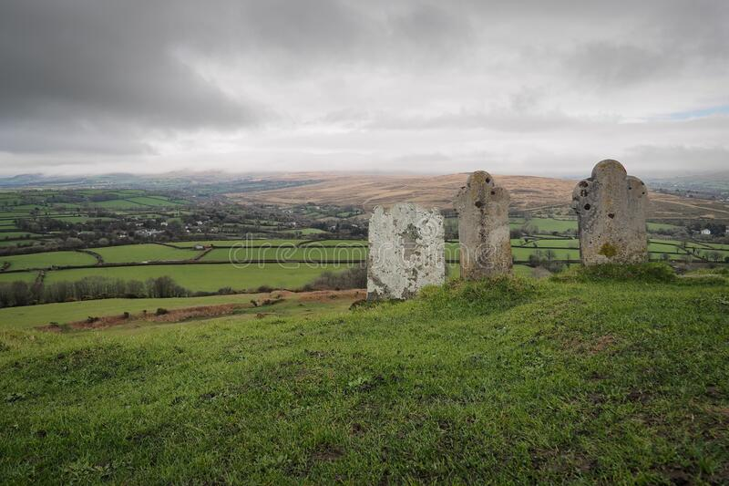 Gravestones at 13th century church St Michael de Rupe, Brent Tor, clouds on hills, Dartmoor National Park, Devon, UK royalty free stock photography
