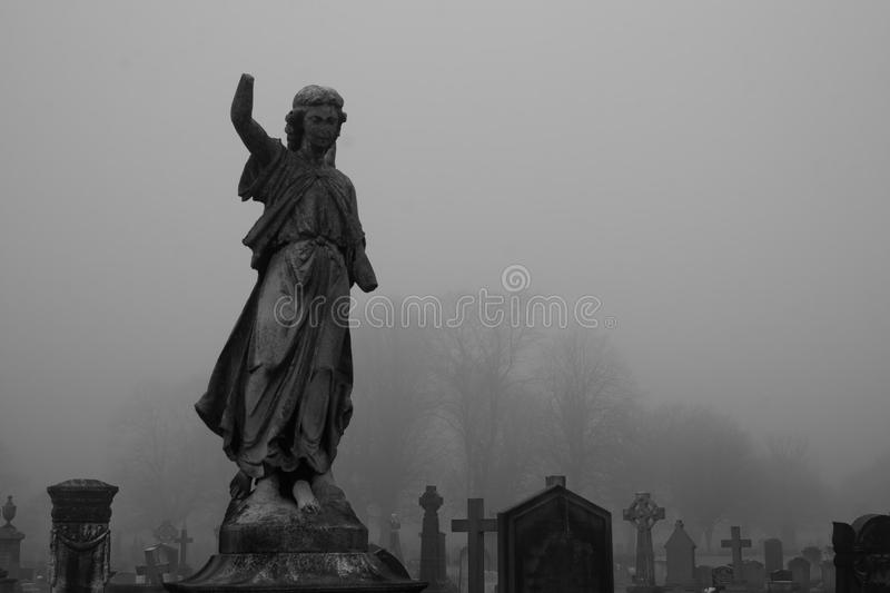 Graveyard statue on a foggy day stock photography