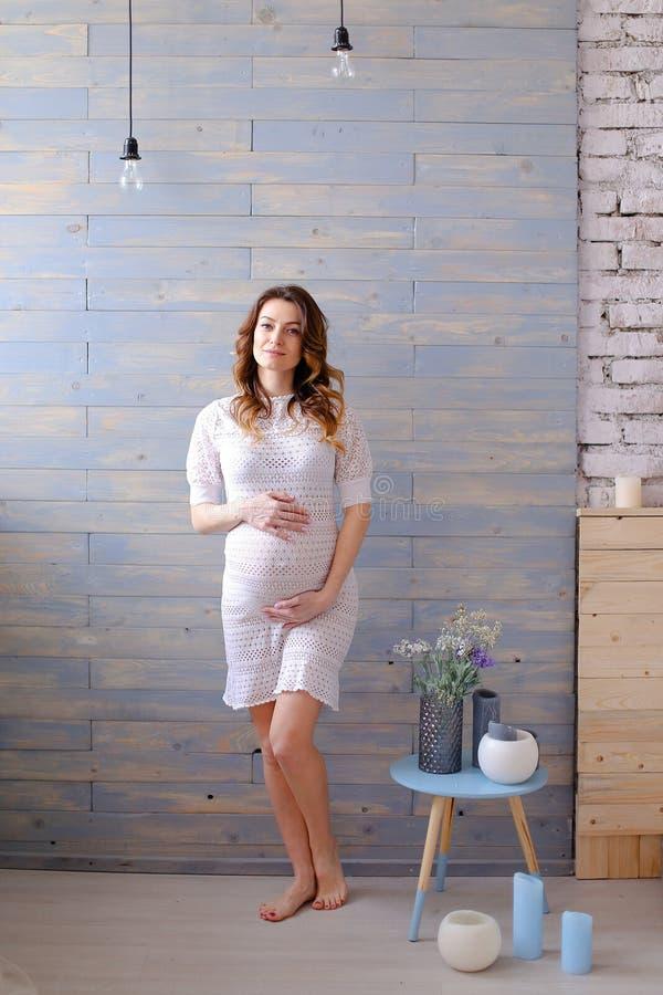 Gravid anseende för ung kvinna i den vita klänningen, trävägg och lampor i bakgrund arkivfoto