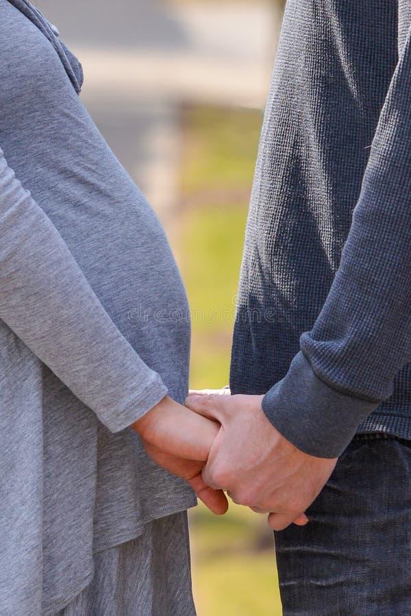 Gravid asiatisk kvinna och Caucasian manpar som rymmer händer som delar ett ögonblick för bliende föräldrar arkivfoton