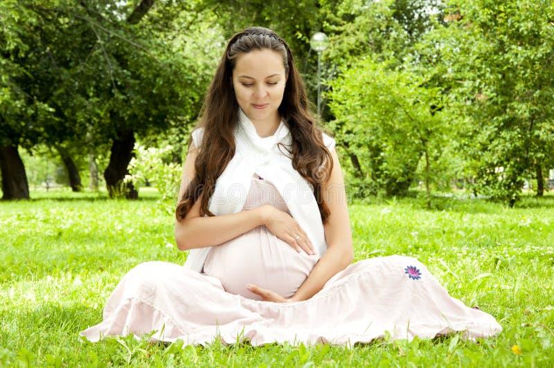 gravid avslappnande kvinna för härlig park arkivfoto