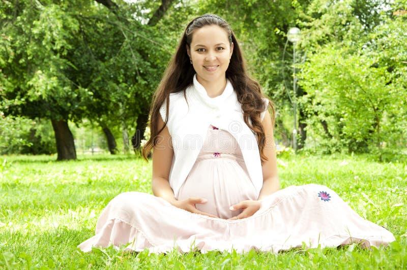 gravid avslappnande kvinna för härlig park arkivbild
