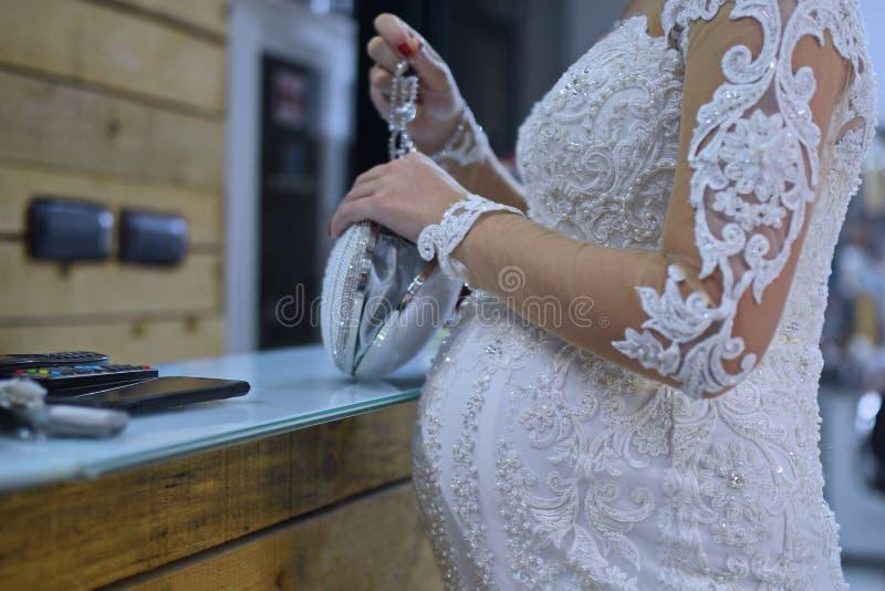 Gravid brud i bröllopsklänning nära tabellen royaltyfri fotografi