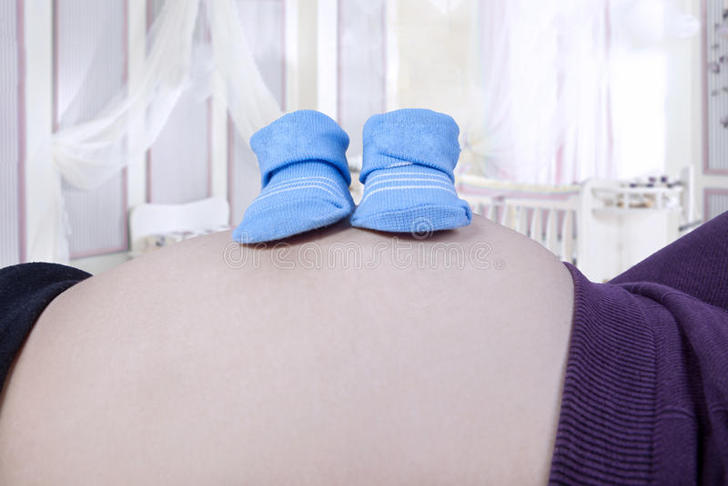Gravid buk med baby med hjärtfelskor arkivfoto