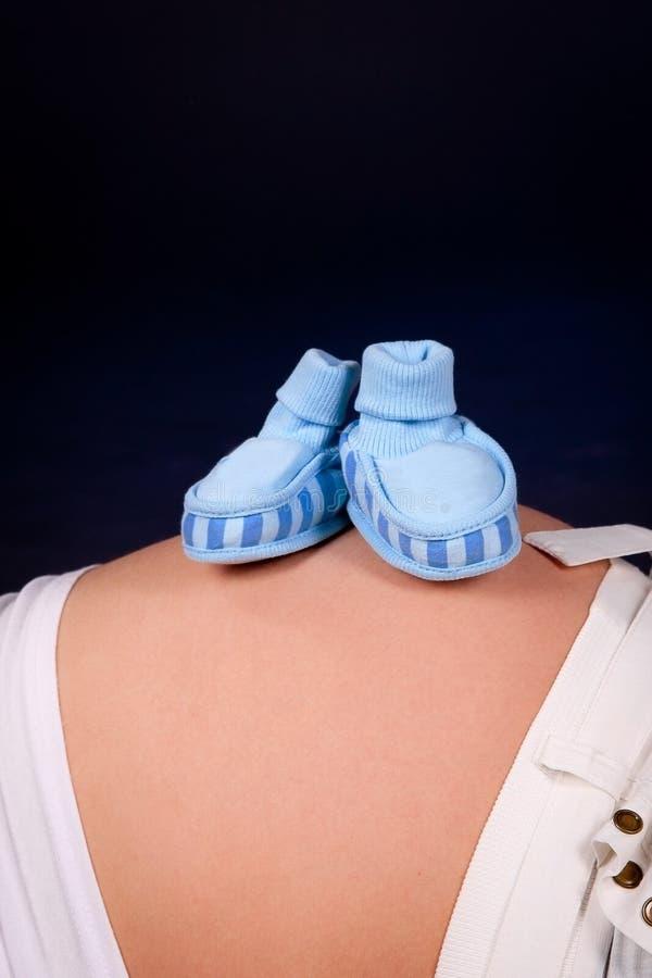 Gravid buk med små blåa skor arkivbild