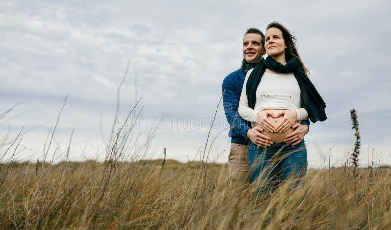 Gravid danandehjärta med händer på den nakna buken med partnern fotografering för bildbyråer