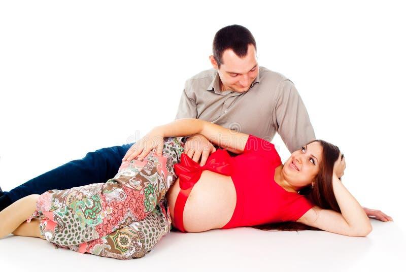 Gravid flicka, lies med ett rött band royaltyfria foton