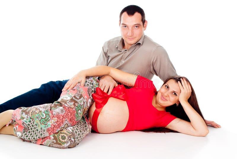 Gravid flicka, lies med ett rött band på hans mage, en maka royaltyfria foton
