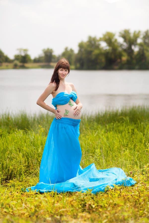 Gravid flicka med fjärilar royaltyfria bilder