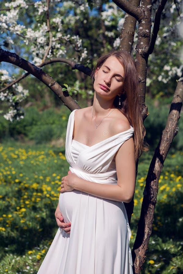 Gravid flicka med långt hår som bär ett vitt klänninganseende royaltyfri foto