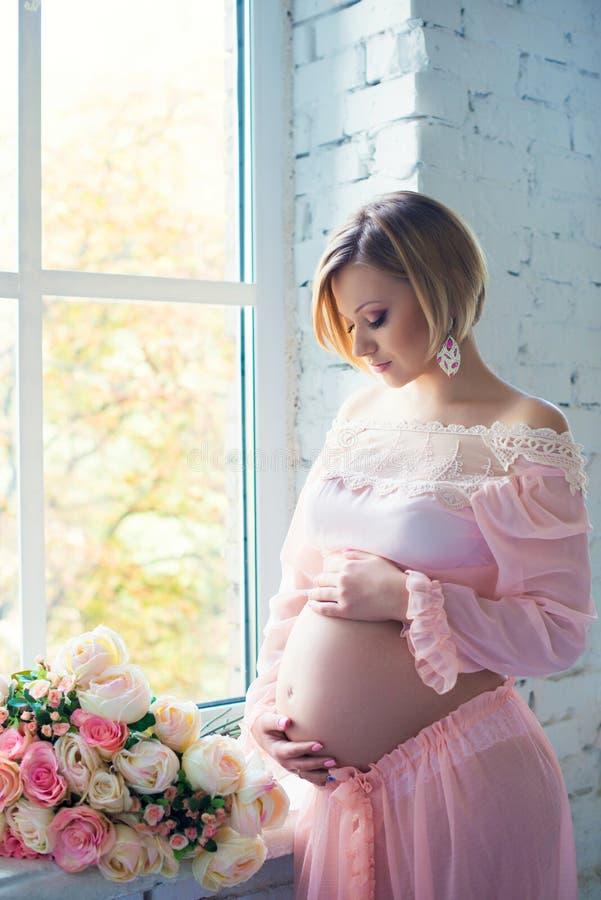 Gravid flicka nära fönstret som kramar magen arkivfoton