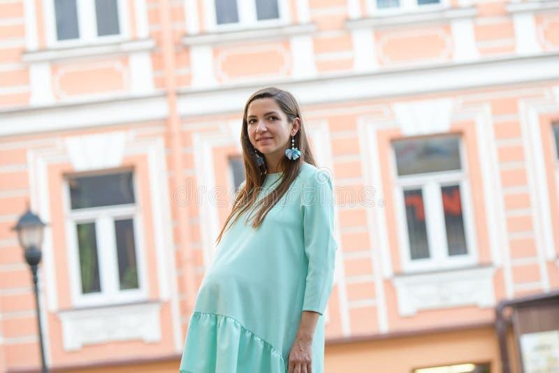 Gravid flicka på bakgrunden av gatafönster Härlig ung gravid kvinna som går till och med stadsgatorna Begrepp av arkivfoton