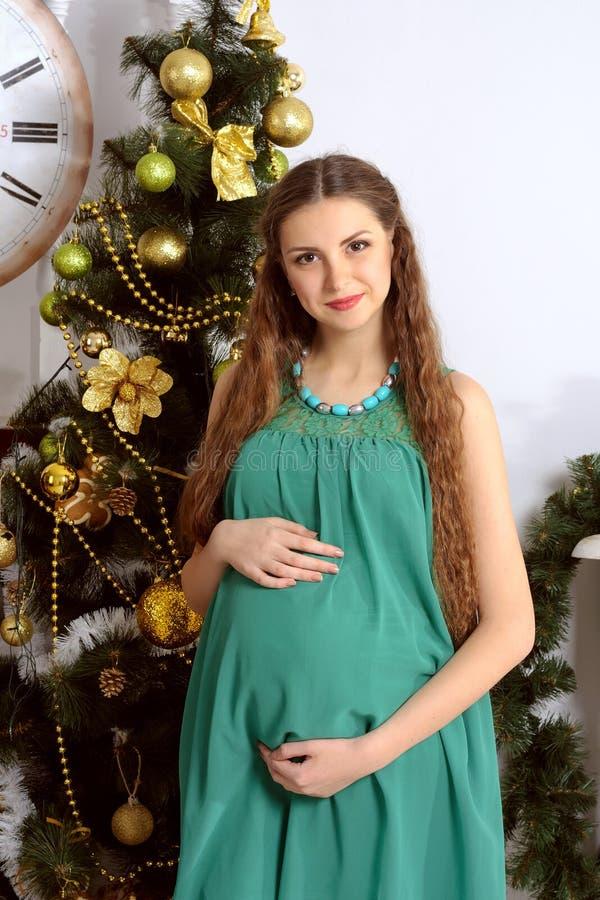 Gravid flicka på en bakgrund av julgranen arkivfoto