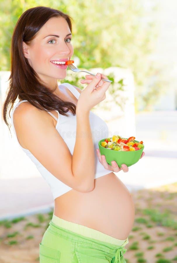 Gravid flicka som har frukosten royaltyfri bild
