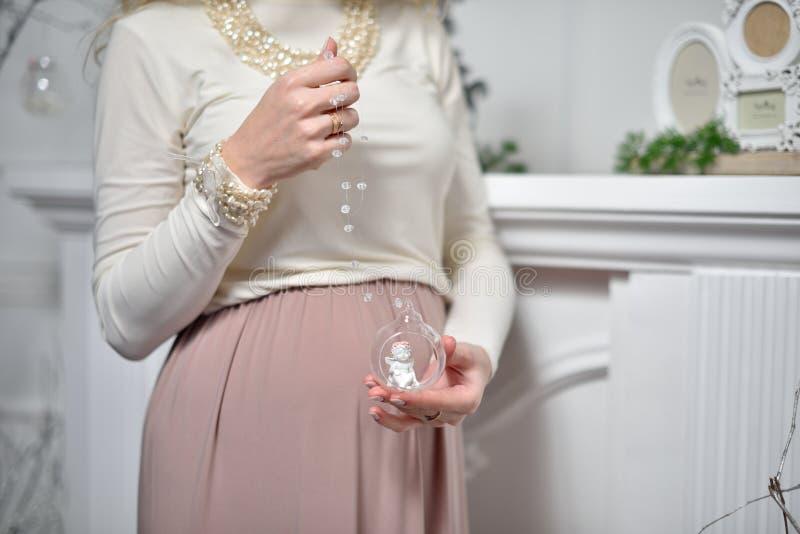 Gravid flicka som rymmer en glass boll med ett ängeldiagram inom royaltyfri fotografi