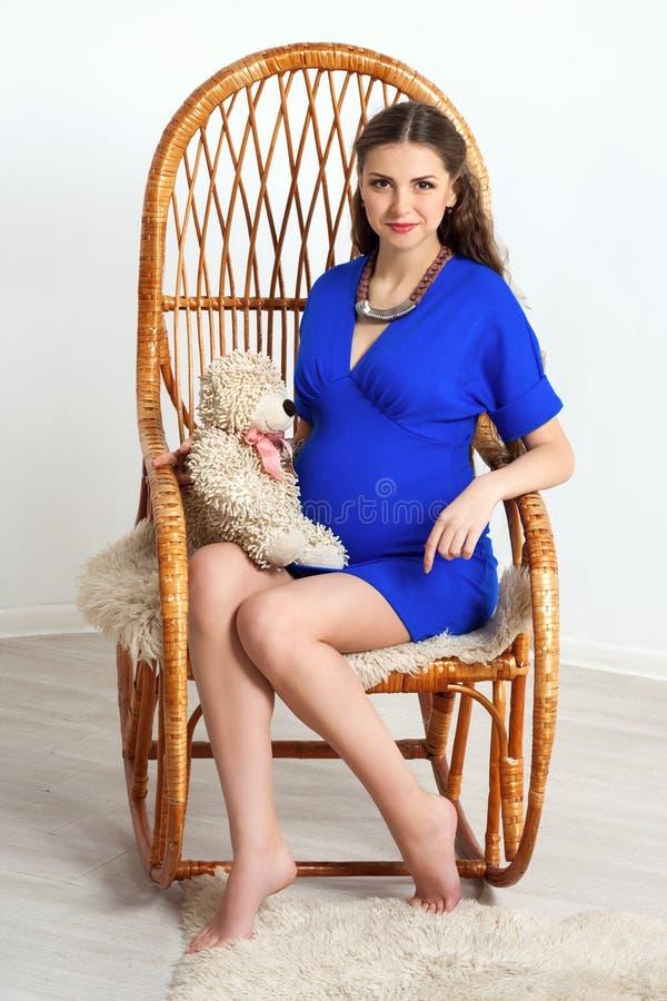 Gravid flickasammanträde i en gungstol royaltyfri fotografi