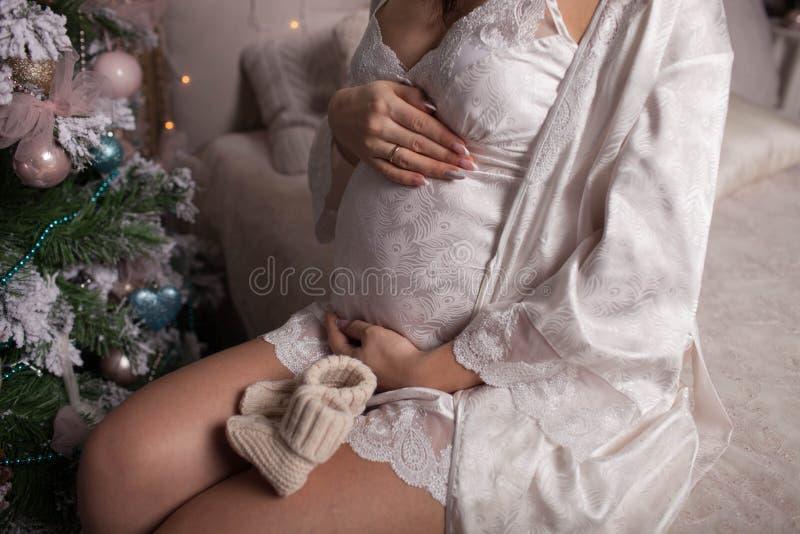 Gravid flickasammanträde på sängen i bakgrunden av julgranen fotografering för bildbyråer