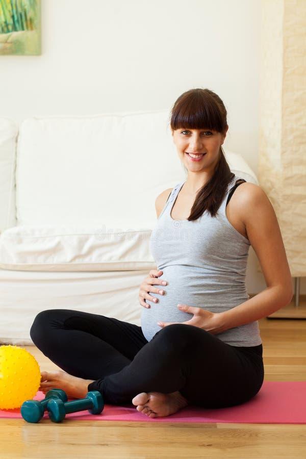Gravid Frau, die Pause von den Eignungsübungen macht stockfotografie