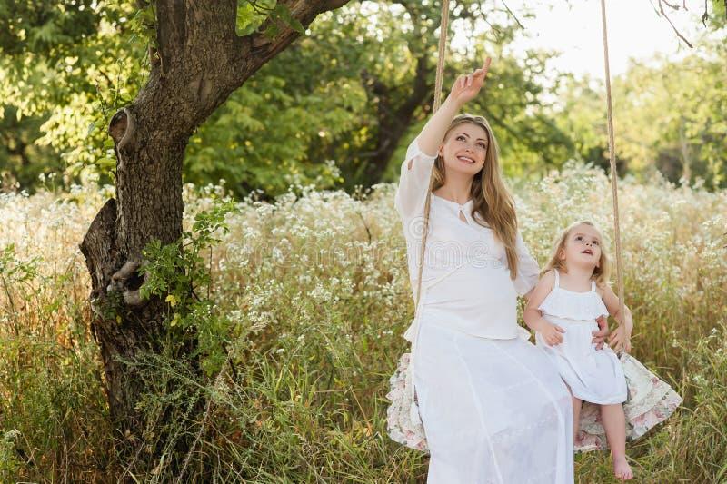 Gravid härlig moder med den lilla blonda flickan i ett vitt klänningsammanträde på en gunga som skrattar, barndom, avkoppling, se arkivbild