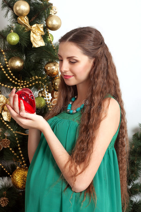 Gravid innehav en leksak i henne händer royaltyfri bild
