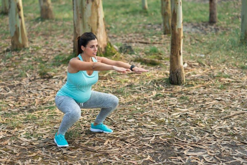 Gravid konditionkvinna som gör utomhus- squats arkivbild