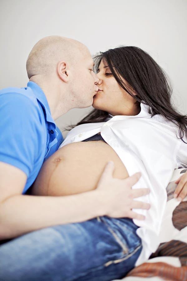 Gravid koppla ihop att kyssa i säng royaltyfria foton