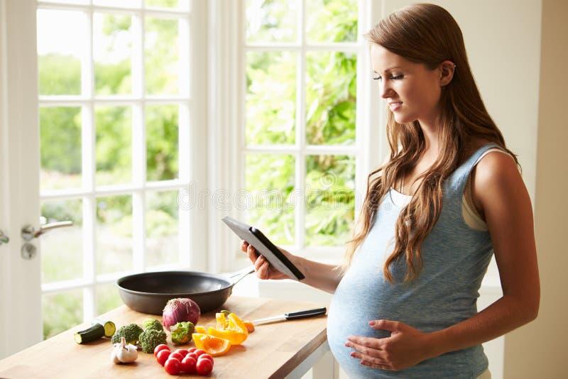 Gravid kvinna efter recept på den Digital minnestavlan royaltyfri foto