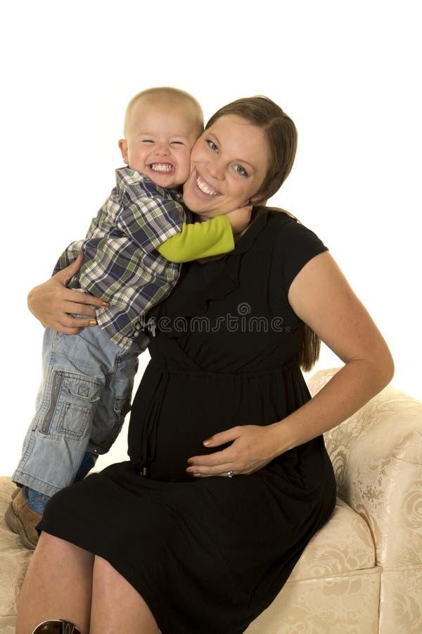 Gravid kvinna i den svarta klänningen som kramas av den unga pojken royaltyfri fotografi