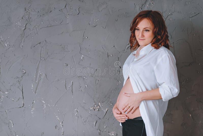 Gravid kvinna i en skjorta för vit man` s, en studiostående De gråa väggarna Ser ner Det finns ett ställe för text royaltyfria foton