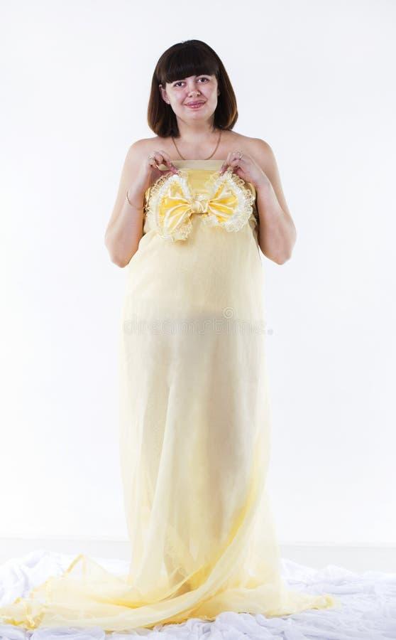 Gravid kvinna i gul klänning arkivfoton