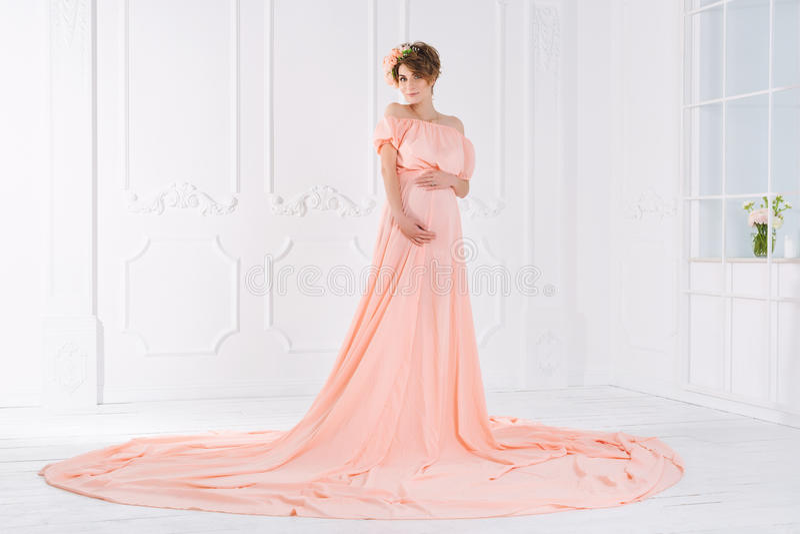Gravid kvinna i rosa aftonklänning skjutit mode arkivfoton