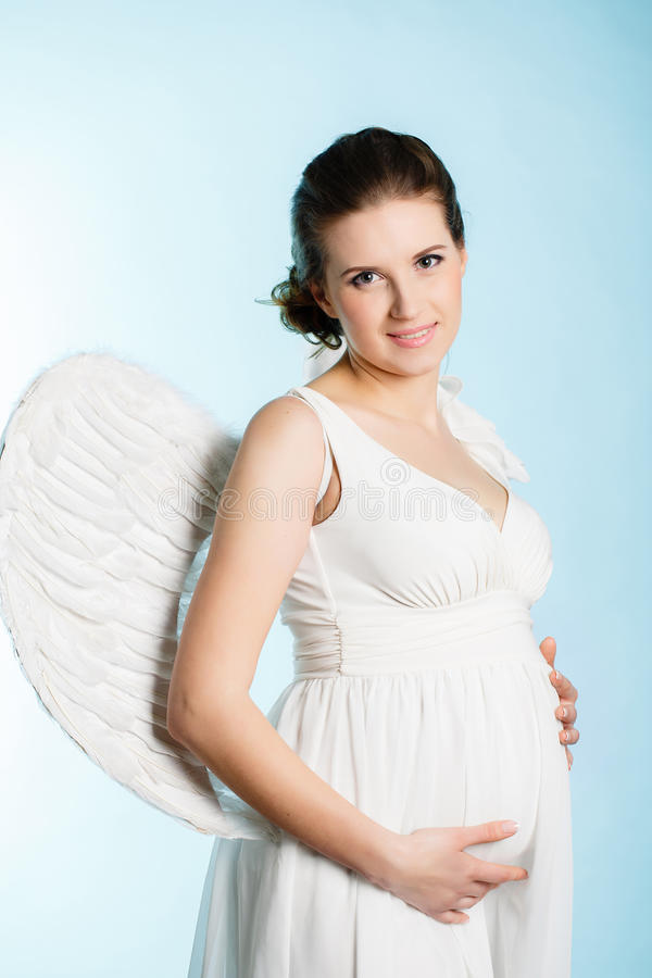 Gravid kvinna med ängelvingar royaltyfri bild