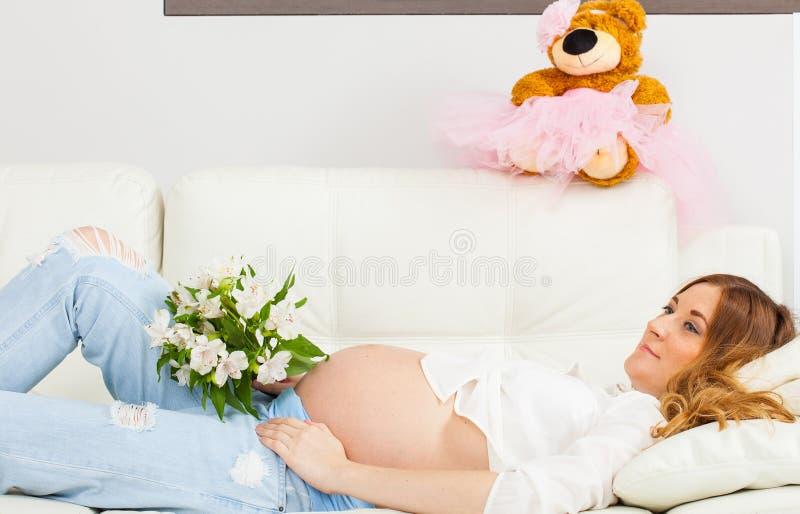 Gravid kvinna med en bukett av blommor royaltyfria foton