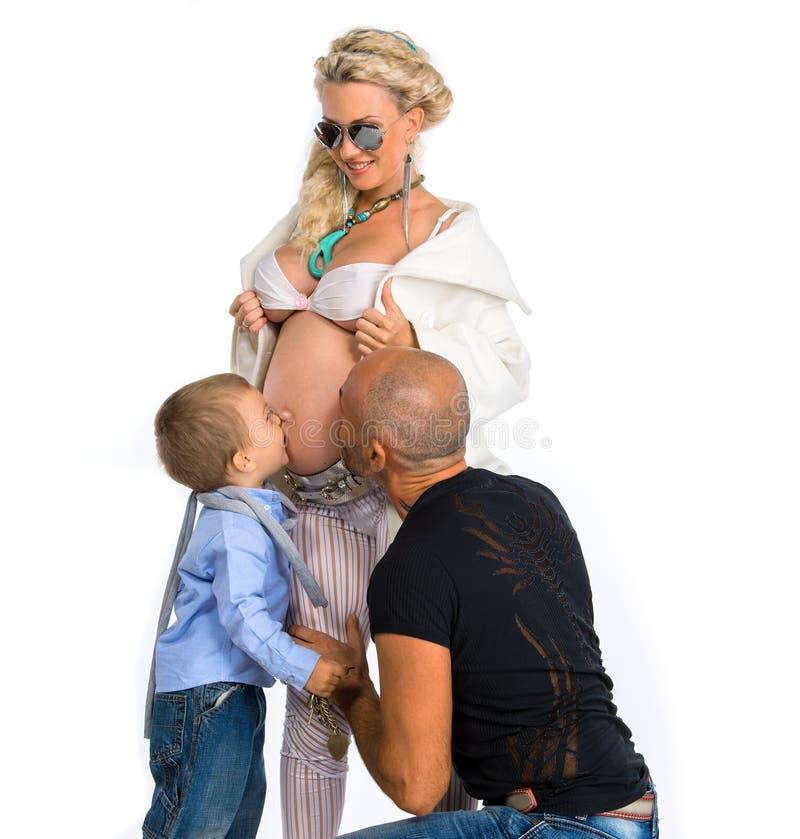Gravid kvinna med hennes make och hennes son som kysser hennes buk royaltyfri foto
