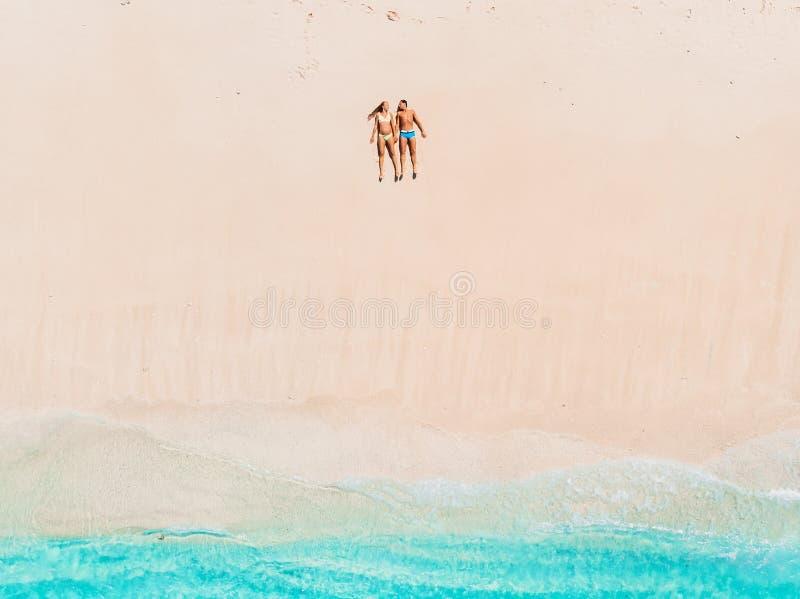 Gravid kvinna med maken på den tropiska stranden med det blåa havet flyg- sikt royaltyfria foton