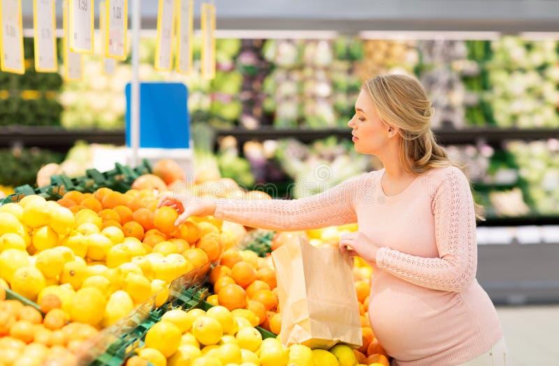 Gravid kvinna med påseköpandeapelsiner på livsmedelsbutiken royaltyfria bilder