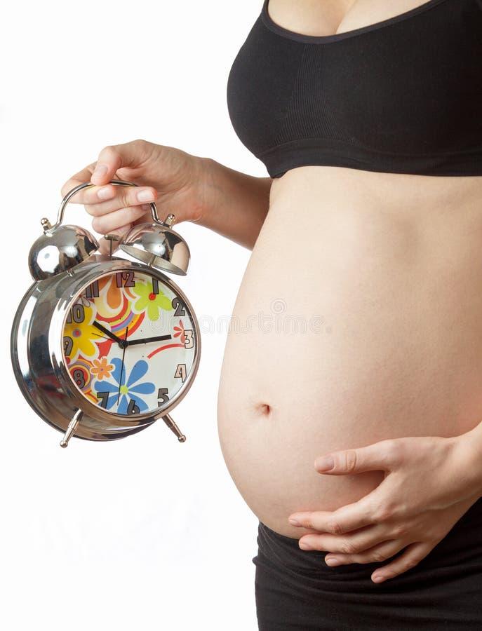 Gravid kvinna med ringklockan royaltyfri foto