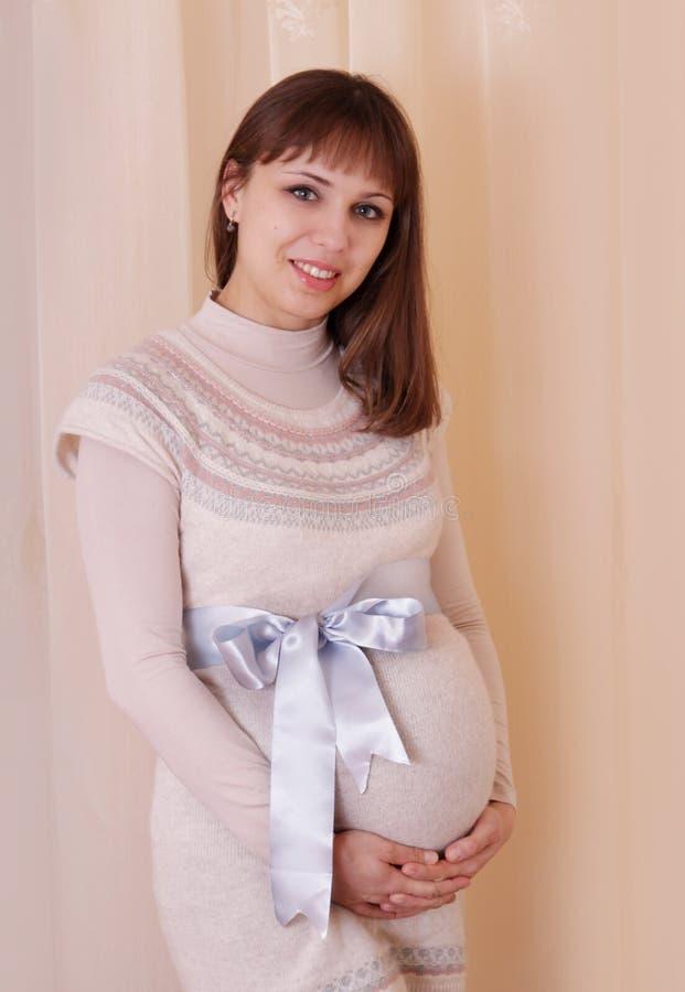 Gravid kvinna med strumpebandsorden på hennes buk arkivfoton