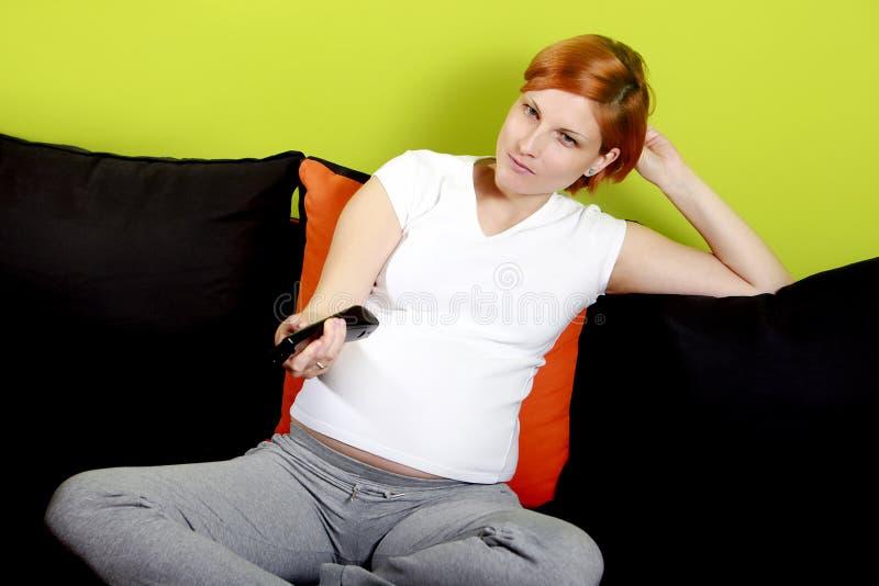 Gravid kvinna med TVfjärrkontroll arkivbild