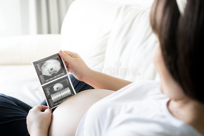 Gravid kvinna med ultraljudsundersökningbilden royaltyfri bild