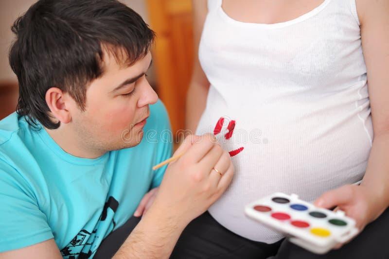 Gravid kvinna och en man som målas på buken fotografering för bildbyråer
