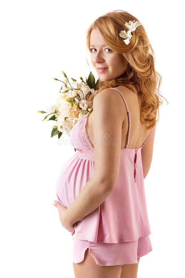 Gravid kvinna och härliga blommor, maternity royaltyfri foto