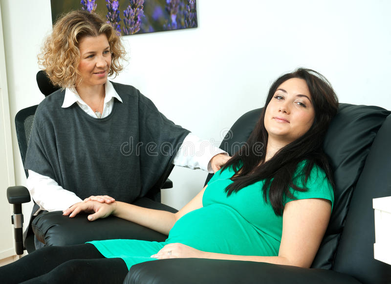 Gravid kvinna och henne terapeut royaltyfri foto